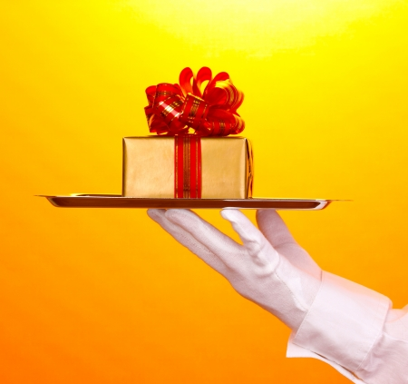 Hand in glove holding silver tray with giftbox on yellow background Stock Photo - 14539583