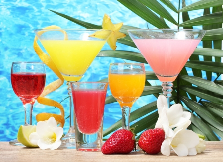 exotic cocktails and flowers on table on blue sea background photo