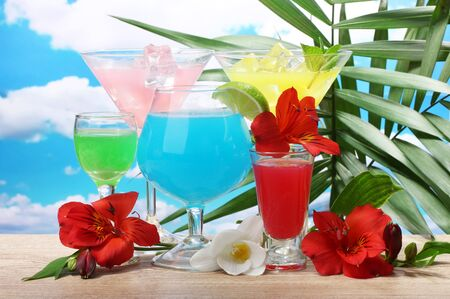 exotic cocktails and flowers on table on blue sky background photo