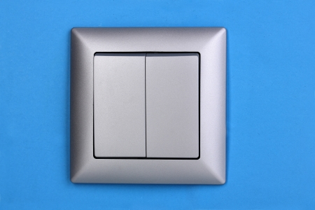Modern light switch on blue background photo
