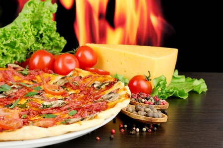 delicious pizza, salami, tomatoes and spices on wooden table on flame background photo