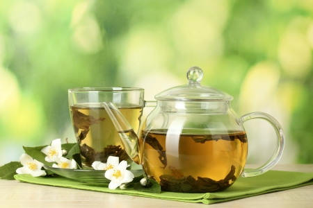 hojas de te: T� verde con jazm�n en taza y la tetera en la mesa de madera sobre fondo verde