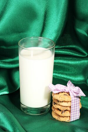 Glass of milk and cookies on green cloth background photo