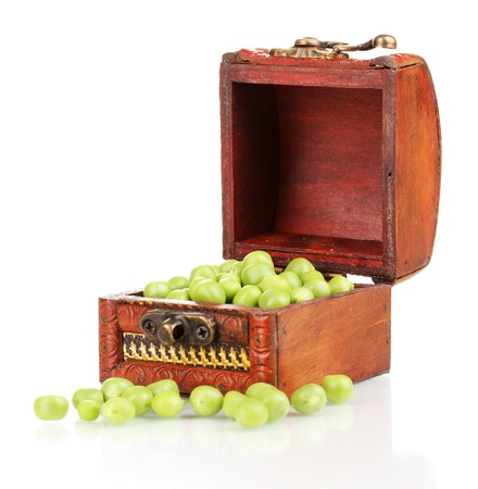 Green peas in wooden chest isolated on white photo
