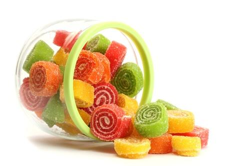 snoepjes: kleurrijke snoepjes gelei in glazen pot op een witte Stockfoto