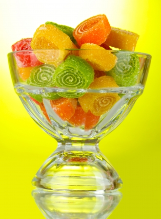 colorful jelly candies in  in glass bowl on green background  photo