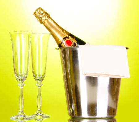 Champagne bottle in bucket with ice and glasses on green background  photo