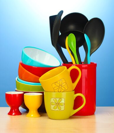 bright empty bowls, cups and kitchen utensils on wooden table on blue background photo