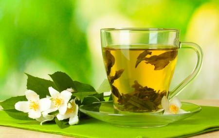 Tasse grüner Tee mit Jasminblüten auf Holztisch auf grünem Hintergrund Standard-Bild
