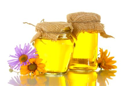 Sweet honey in jars and flowers isolated on white photo