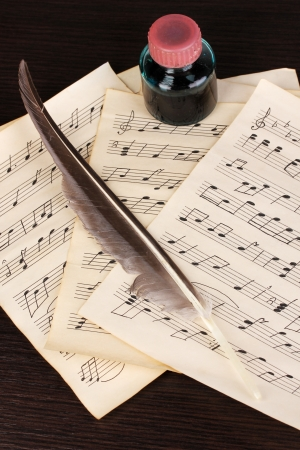 musical score: Musical notes and feather on wooden table