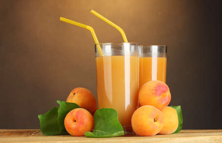 glasses of apricot juice on wooden table on brown background photo