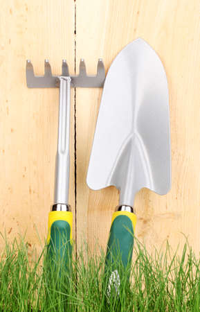 Green grass and garden tools on wooden background photo