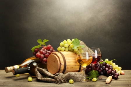 barrel, bottles and glasses of wine and ripe grapes on wooden table on grey background Stock Photo