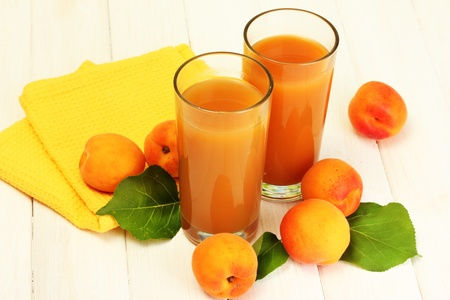 glasses of apricot juice  and fresh apricots on white wooden table photo