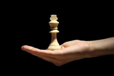 Chess piece in hand isolated on black photo