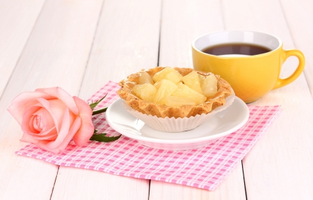 sweet cake with cup of tea on wooden background photo