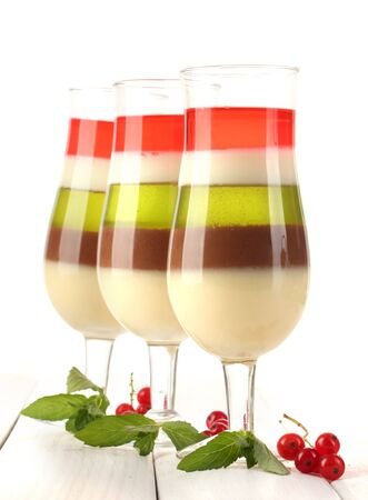 fruit jelly in glasses, berries and mint on wooden table photo