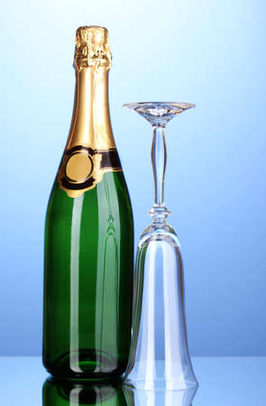 Bottle of champagne and goblet on blue background photo