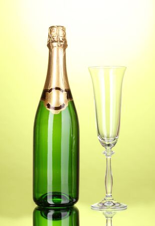 Bottle of champagne and goblet on green background photo