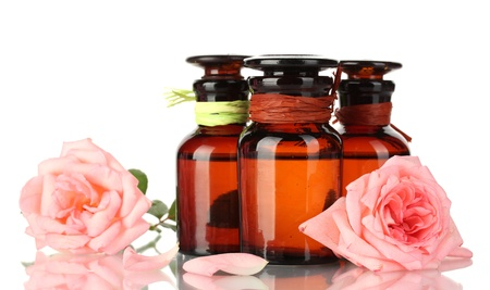 perfume oil: bottles of oil and roses isolated on white