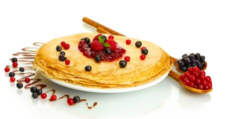 Delicious pancakes with berries and jam on plate isolated on white photo