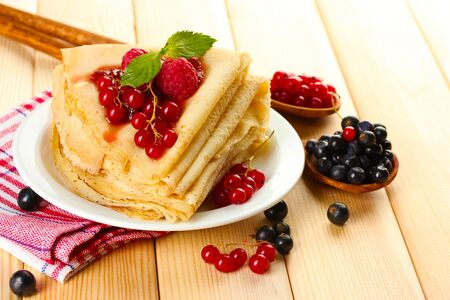 Delicious pancakes with berries and jam on plate on wooden table photo