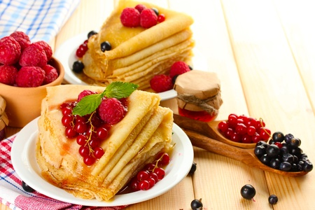 Delicious pancakes with berries, jam and honey on wooden table photo