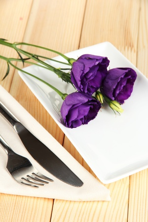Tableware with flower on bright napkin close-up photo