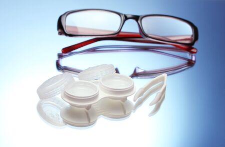 lentes de contacto: gafas, lentes de contacto en los contenedores y las pinzas sobre fondo azul