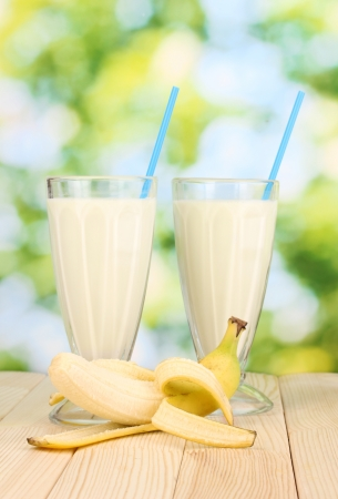 Banana milk shakes on wooden table on bright background photo