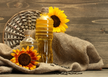 oil in bottles, sunflowers and seeds, on wooden background photo