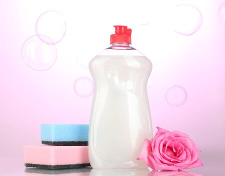Dishwashing liquid with sponges and flower on pink background photo