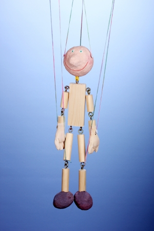 Wooden puppet on blue background photo