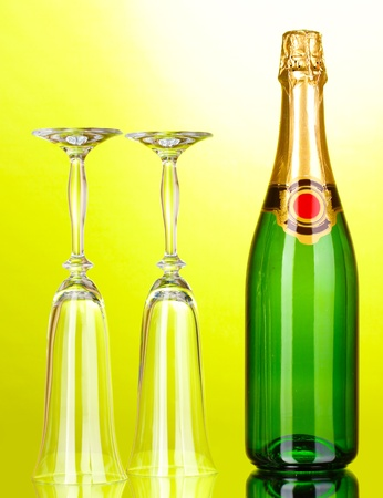 gold capped: Bottle of champagne and goblets on green background