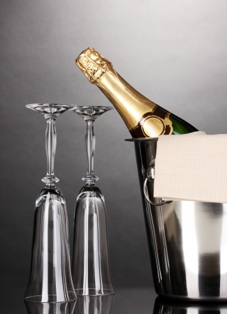 Champagne bottle in bucket with ice and glasses on grey background  photo