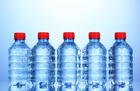 plastic bottles of water on blue background photo