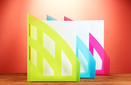 secretary tray: Colorful trays for papers on red background close-up