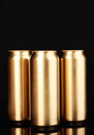 golden cans isolated on black photo