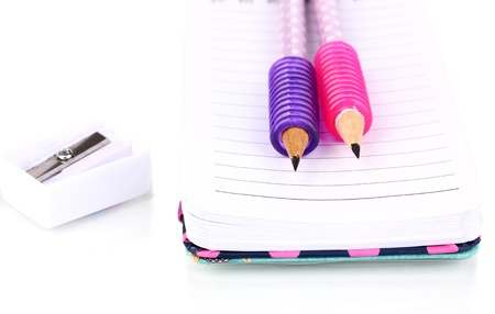 undermine: Pencils, pencil sharpener and notepad isolated on white Stock Photo