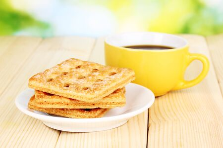 Cup of coffee and cookies on wooden table on bright background photo