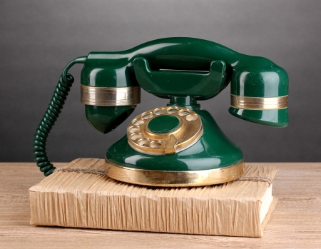 Retro phone standing on book on wooden table on grey background photo