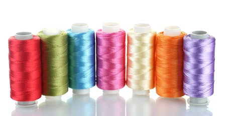 textile industry: bright bobbin thread isolated on white