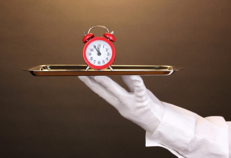 Hand in glove holding silver tray with alarm clock on brown background photo