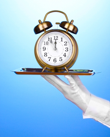 Hand in glove holding silver tray with alarm clock on blue background photo