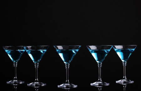 nightclub bar: Blue cocktail in martini glasses isolated on black Stock Photo