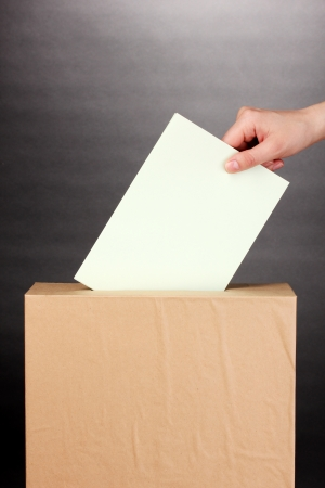 Hand with voting ballot and box on grey background Stock Photo - 14694196
