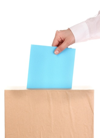 Hand with voting ballot and box isolated on white photo