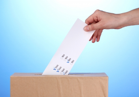 Hand with voting ballot and box on blue background Stock Photo - 14712078