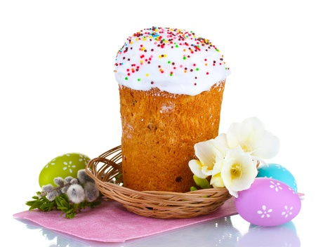 Beautiful Easter cake in basket, colorful eggs and flowers isolated on white photo